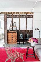 书房中,一对法式鸟笼位于一张购自日韩古董店的五斗橱上,旁边两把黑色的木椅是来自奥地利的古董家具,灰色的沙发是意大利制造,玫红的渐变色地 毯