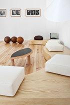 波浪形木长椅和黑色小木桌是Janette Laverrière的设计,远端长椅上的黑色石头来自Coustin Hölle,几只真皮的老式皮球散落在墙角。低矮的波浪形长凳展现了一种席地而坐的随性,洁白的软垫则中和了整个空间的硬朗感。