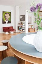 """红色皮沙发与墙上的油画产生撞色的效果,近处的可发光圆桌""""Telling Stories""""和座椅由概念艺术家Liam Gillick设计,桌上的白色花瓶则来自Martin Freyes。当代艺术是一种全球性的现象,迫使我们改写传统叙事方式, 同时创造出新的文化。"""