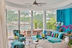 底层客厅中拥有一片弧形落地门窗,让深水湾和周围山丘的景色 尽收眼底。当门窗打开,清新的海风迎面吹来,家中又能与自然亲密接触。这里的家具大都在香港本地制作,咖啡桌上的猫头鹰玻璃摆件由艺术家Claude Venard创作,20世纪60年代中期的Murano玻璃艺术家为其着色。