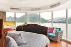 """环绕式的玻璃幕墙让家中拥有180度的山峦海滨视野,彰显出香港作为一个热带岛屿的自然魅力。主卧室中也配置了弧形玻璃窗,法式古董床上精雕细琢的床头和床尾板都是在香港定做的,床上用品品牌为Ralph Lauren。轮船主题的油画出自新西兰艺术家Rob Tucker之手,是在香港""""买得起艺术节(Affordable Art Fair)""""上猎获的。"""