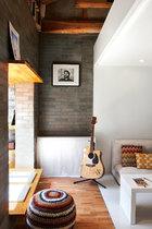 一层的小休息区与室外天井相连,可坐可卧,在这里睡个午觉,再惬意不过。从玄关通过开放式厨房,就来到了舒适的小休息区。 小休息区做成了榻榻米式,一张软垫就能当成随性的沙发。墙上的摄影作品是从宝姐之前开的咖啡馆搬过来的。条纹毛线球形软垫来自UCCA。吉他可弹也可作为 家中的装饰。