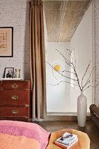 主卧室的另一侧,墙上挂的手绘海报由Mark Davidson创作于1970年,下方的小柜是维多利亚女王时代的红木家具,小柜上的两只手工烛台来自丹麦设计师Jens Quistgaard。落地玻璃窗前的白色花瓶来自Spin,窗外楼梯间墙面上的生鸡蛋树脂雕塑由李金国创作。