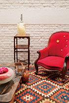 """二楼夹层上的客厅一角,红色国旗图案的扶手椅是Ben自己在维多利亚时期的经典Spoon Back椅上再创意而成的""""中国椅""""(China Chair)。一侧的木质边几是爱德华七世时期(1841~1910)的红木家具,来自英国,边几上面的云雾灯(Cloud Lamp)是Ben在设计师李金国的树脂作品基础上安装LED光源而完成的设计,民族风格的地毯则是一件生产于约1900年的古董,来自阿富汗。"""