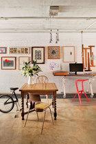 楼下Alex的工作室中,有一张大约可以追溯到1900年的英国橡木的折叠餐桌,远处工作台前的红色Miura坐凳由Konstantin Grcic设计,Plank出品。
