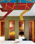餐厅的天花板和墙面上布满了英国画家David Tremlett所创作的各种几何图形,屋顶壁画同样是他的现场作品。后现代主义风格的餐厅搭配David Tremlett在墙壁上绘制的几何图形以及5根墩柱撑起的墙体造型,穿过墩柱可直接进入右边的厨房。