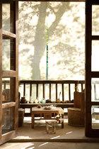 微风吹起用来遮挡骄阳的帘布,那一抹摇动的树影足以让在此品茗的 人身心沉醉。李见深工作室中喝茶的空间,婆娑树影倒映在帷幔上,帘内的木质美人靠(栏杆)既保证了安全,又十分唯美。在这里喝茶时总有帘外的水声相伴。
