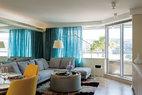 [After] 客厅中JAB湖蓝色薄纱窗帘为灰色的B&B Italia家庭旅馆式L形拐角沙发和Temperature Design脚凳增添了一抹亮色。手工羊毛丝毯上摆放着直径900mm的圆形橡木茶几。墙上装饰的大面积落地镜,不仅营造出更加宽敞的视觉,更将海港景色倒映进了房间。