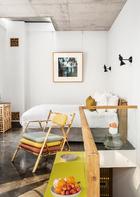 """新式的""""峨眉""""客房二层,能清楚 地看到酒店在空调通风口、暖气片上都细心装饰了木格栅。两只抽象小鸟形状的黑色壁灯是Atelier Areti品牌的Bird Lamp。这间客房中选用的艺术品来自著名演员刘烨的妻子Anais Martane,她的摄影作品《桥上伞》(An Umbrella on the bridge)和《胡同花》 (Hutong Flower)刻意运用不对焦的拍摄方法虚化了场景,让平凡生活显出朦胧之美。"""