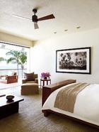 主卧室与户外阳台开放相连,一侧的墙上挂着摄影师BowenSmith拍摄的风景照片,小桌子来自Ralph Lauren Home。