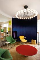 很大的面积留给客厅,一红一橙两张咖啡桌将客厅分为两个部分,埃菲尔铁塔就优雅地立在窗外。客厅天花板上的大吊灯是Gino Sarfatti的设计。