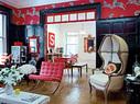 """客厅以及主人的餐厅兼书房中,黑红主色调以及各种风格的混搭效果非常惊艳。天然白的经典连帽座椅购于纽约Restoration Hardware,一旁是红色的""""巴塞罗那""""椅,靠墙的金色巴洛克式镜子购自Horchow。"""