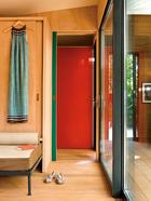所有房门都是可滑动移门,这样可以更好地利用空间。第二个卧室,摆放着可以绕着挂衣壁柜部分旋转的矮床,壁柜上挂着一条路易威登2014 Icons Eté系列女裙。