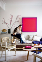主人兼设计师Marta坐在一张在Jon Urgoiti购买的用竹子和黄铜制成的床上。墙上挂着在Javier López购买的José María Yturralde的彩绘板。