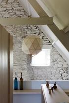 主卧中的一面墙壁采用石灰石材质,近处的储物柜上,KristianVedel制作的木头小鸟来自PopCorn,墙角的两只玻璃花瓶购买于Conran Shop,日式的木框纸吊灯来自Sentou。