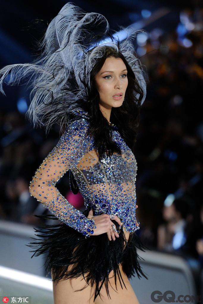 首次上秀的Bella Hadid就有一对翅膀两套秀服,另一套是Secret Angel主题 ,在透视纱衣上镶满了蓝色的钻石,黑灰色的羽毛翅膀更加耀眼妩媚。